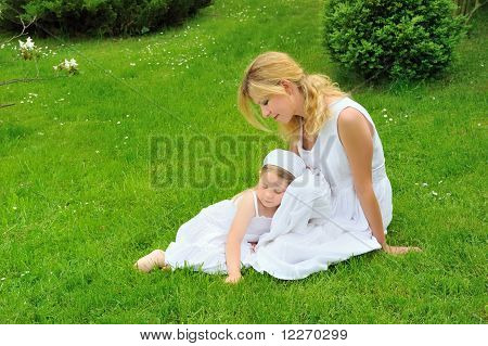 Young mother and daughter resting in meadow