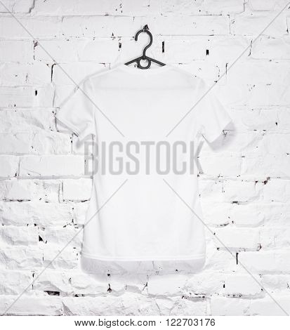 brick whitewashed wall with white t- shirt on hanger