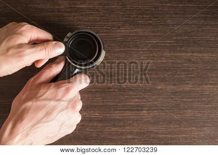Man preparing ground coffee in brew unit for brewing on kitchen counter. Top view image