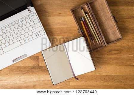 Workspace mock-up with notebook, laptop and pencils. Top view image creative person desk with drawing or writing stuff