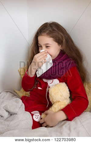 Little girl lying in bed with flu at home. Pretty lady blowing her nose and holding teddy bear.