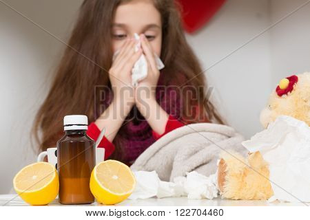 Fever, cold and flu concepts. Close-up of medicines represented on table while pretty sick girl blowing and cleaning her nose in tissue in on the background.