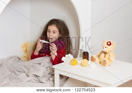 Fever, cold and flu concepts. Portrait of surprised little lady laying in her bed and looking at thermometer with high temperature.