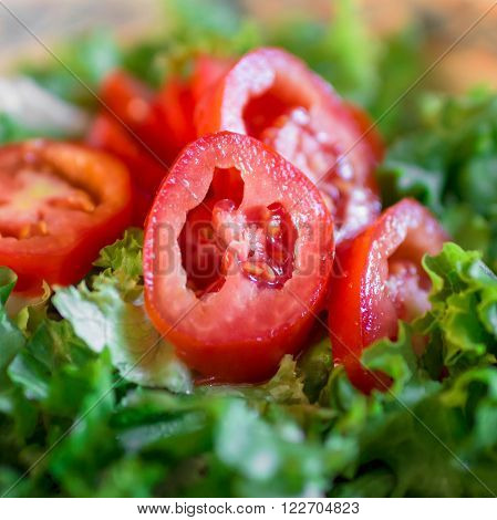 Extreme close-up of a salad with lettuce and fresh tomatoes.