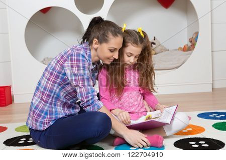 Mother reading book to her daughter while resting on floor at home. Little girl listening to her mother very attentively.