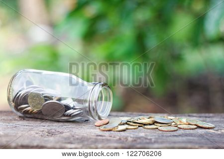 A glass jar filled with coins in outdoor setting ** Note: Shallow depth of field
