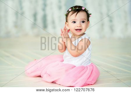 little girl sitting on the floor in a smart dress
