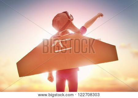 Little child girl plays astronaut. Child on the background of sunset sky. Child in an astronaut costume plays and dreams of becoming a spaceman.