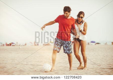 Young couple playing football on the beach at sunset.