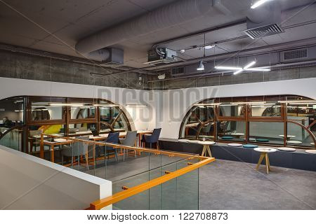 Coworking in a loft style. Two white walls with brown rounded windows. Upper parts of walls are concrete. Close to left wall there are light tables with orange legs and gray and blue chairs. There are pens, a plant, notebooks and a laptop on the tables. N