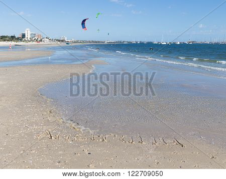 Australia inscription on the sand with shells on a large beautiful Australian beach and unrecognizable people go kite surfing and beautiful bright sails flying over blue sea with small waves Australia