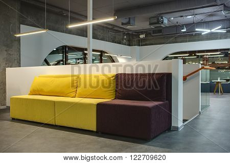 Yellow-brown sofa with pillows on the white low wall background. Close to the sofa there is a begin of stairs with orange handrail. Behind the sofa there is a hall in a loft style with white walls and brown rounded windows. Upper parts of wall are concret