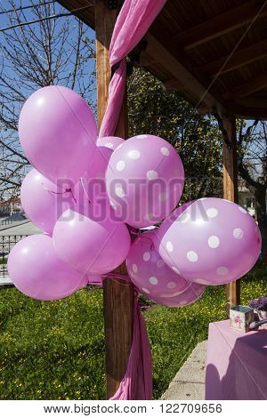 pink balloons tied to a wooden kiosk