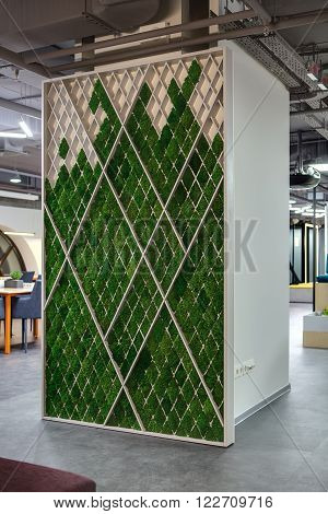 Ornamental light stand decorated with green grass on the white wall background. It is standing in centre of hall in a coworking. On the floor there are gray tiles. At the top there are communications and lamps.