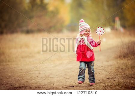 little girl playing pinwheel toy walking on autumn landscape