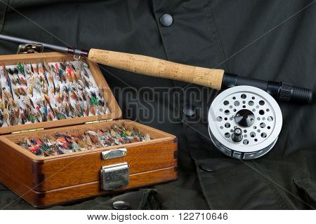 Fly fishing rod reel and flies on outdoor coat background