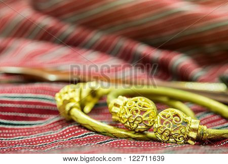 Antique gold bracelets Asian traditional style on red nainsook blur background. Selective focus.