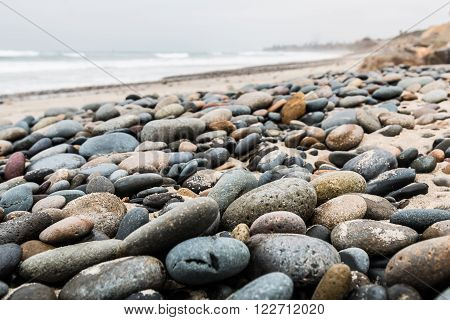 Close-up view of stones scattered about the beach at South Carlsbad State Beach in San Diego, California.