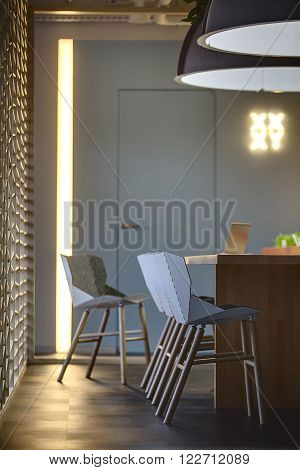 Table with a laptop on it and chairs standing near the table. Two large lamps over the table. On the left there is an ornamental wooden partition. On a background there are a wall with a door and a glowing pointer. Place for coworking.