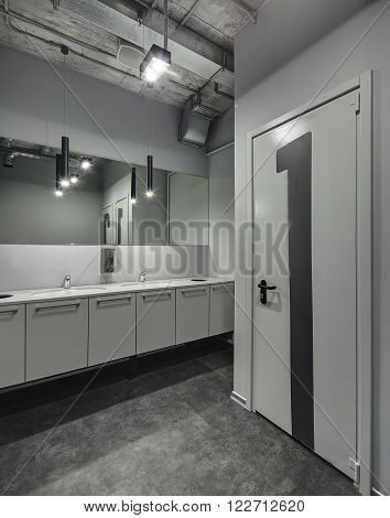 Gray colored restroom. At the right side there is a door with big number 1 on it. Doors and walls reflected in the mirror. There are two white sinks with cases under them. Between sinks there is a wall-mounted soap dispenser. At the top there are black la