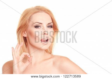 Beautiful blonde girl 20-25 year old showing okay by fingers over white. Closeup portrait of young woman posing in studio. Looking at camera. Isolated.