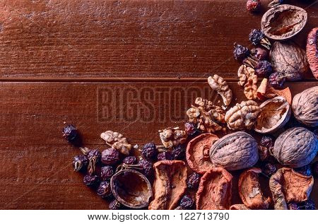 Dried fruits, walnuts and dried berries rose hips on the wooden table. Can be used as background.