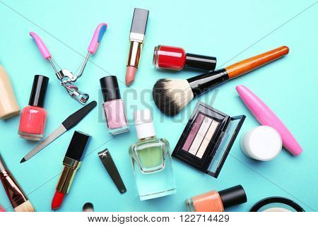 Decorative makeup cosmetics and manicure tools on turquoise background