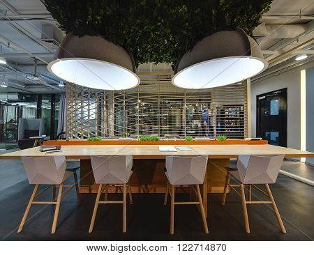 Interior in a loft style. Wooden table with stand for office supplies. There are grass decorations on the stand. Above the table hang large lamps with artificial leaves. There are notebooks on the table. Four chairs are near the table. Behind the table th