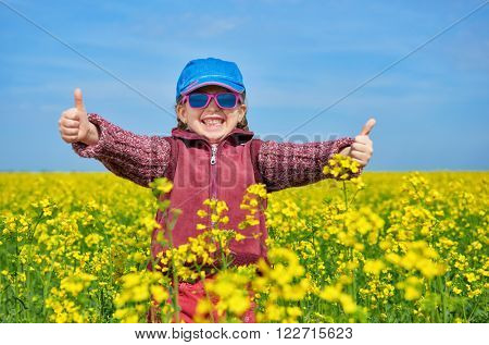 girl child in rapeseed field with bright yellow flowers, spring landscape