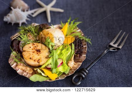 Fresh seared sea scallops salad with mango radish avocado on scallop shell with fork on the side