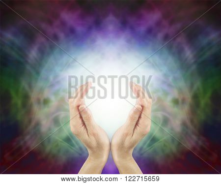 Pranic Healing Energy - female hands cupped around a ball of bright energy on a beautiful subtle multi colored energy field background with plenty of copy space