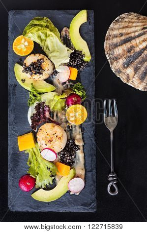 Pan seared scallops with salad avocado radish mango and black caviar on a stone plate top view vertical composition