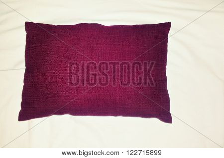 a violet cushion lost in unmade bed
