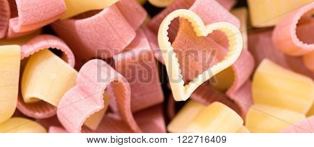 Red and yellow heart shaped pasta top view letterbox format food background