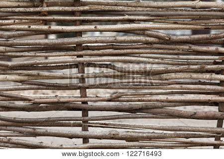 Lath fence of twigs wooden texture closeup