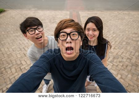 Korean friends making funny faces when taking selfie