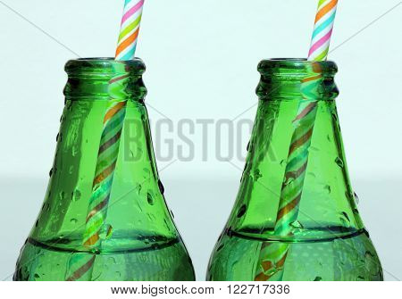 Close up view of two Glass Bottle of Water Necks with color striped straws at sunny summer day.