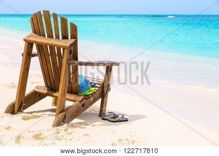 Wooden beach chair with hat and slippers and sunglasses at tropical beach summer holiday concept