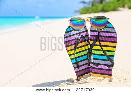 Multicolored flip-flops and sunglasses on a sunny beach. Tropical beach vacation and travel concept vertical composition