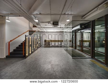 Reception hall in a coworking. On the left there is black stairs with orange handrails. Right of the stairs there is a big stand. At the end of the hall there is a reception desk. On the right there are entrance doors.