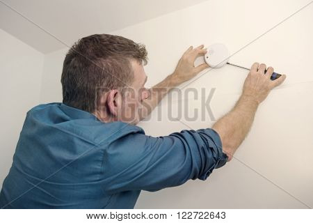 handsome man repairing a smoke detector in a hallway