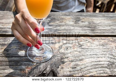 Woman's hand with red fingernails holding a glass of orange juice closeup outside on a sunny day