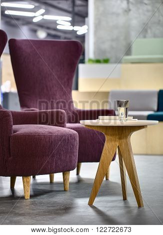 Two purple armchairs with small round wooden table. There is a glass of water and books on the table. On the blurry background there are benches, lamps and concrete wall. On the floor there are gray tiles.