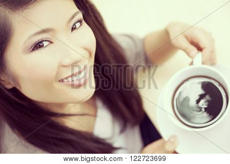Instagram style portrait of beautiful young Chinese Asian woman with perfect teeth smiling drinking tea or coffee from a white cup and saucer