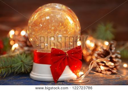 Christmas snow globe with red bow and garland lights on wooden background