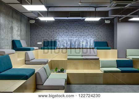 Light wooden benches with multi-colored seats. Seats are made up of pillows. At the back on bench there is a digital clock which made from the transparent rectangles. Left wall is from concrete and back wall is from brick. There are several niches on the