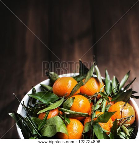 Ripe Mandarin fruit on old rustic look timber / Fresh mandarin oranges fruit with leaves