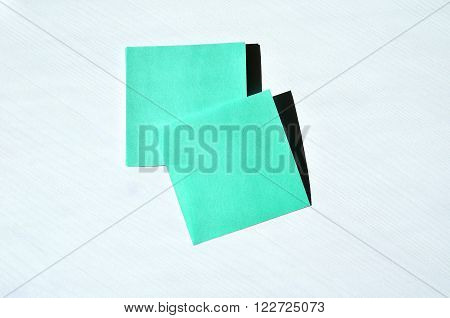 Green memo papers with free space for text on the white wooden surface. Memo concept business background.