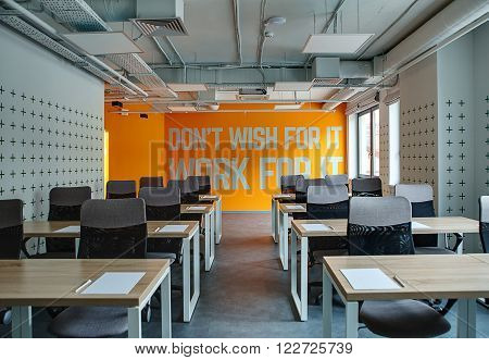 Room for lecture with a lot of tables and chairs. Tables are wooden with gray legs. Chairs are black with gray. There is a paper sheet and a pen on each table. Side walls are white with prints. Back wall is orange with white inscription. On the right side