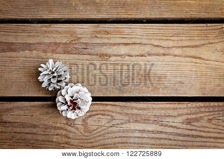 Beautiful simple winter background with pine cones on wooden texture